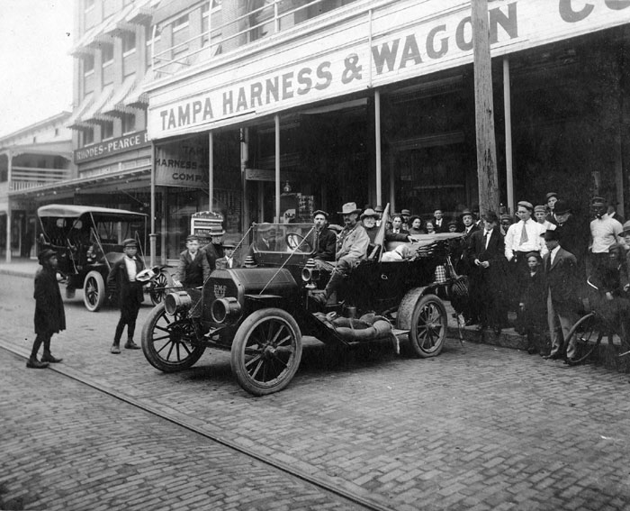A black and white photo of the people and cars in front of the Tampa Harness and Wagon Co. at 1007-1009 Franklin Street, taken around 1910.