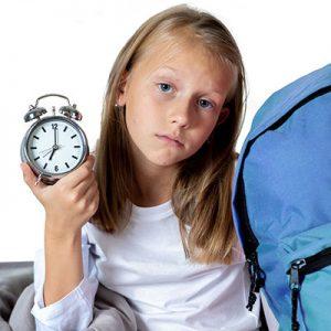 Sad girl with alarm clock